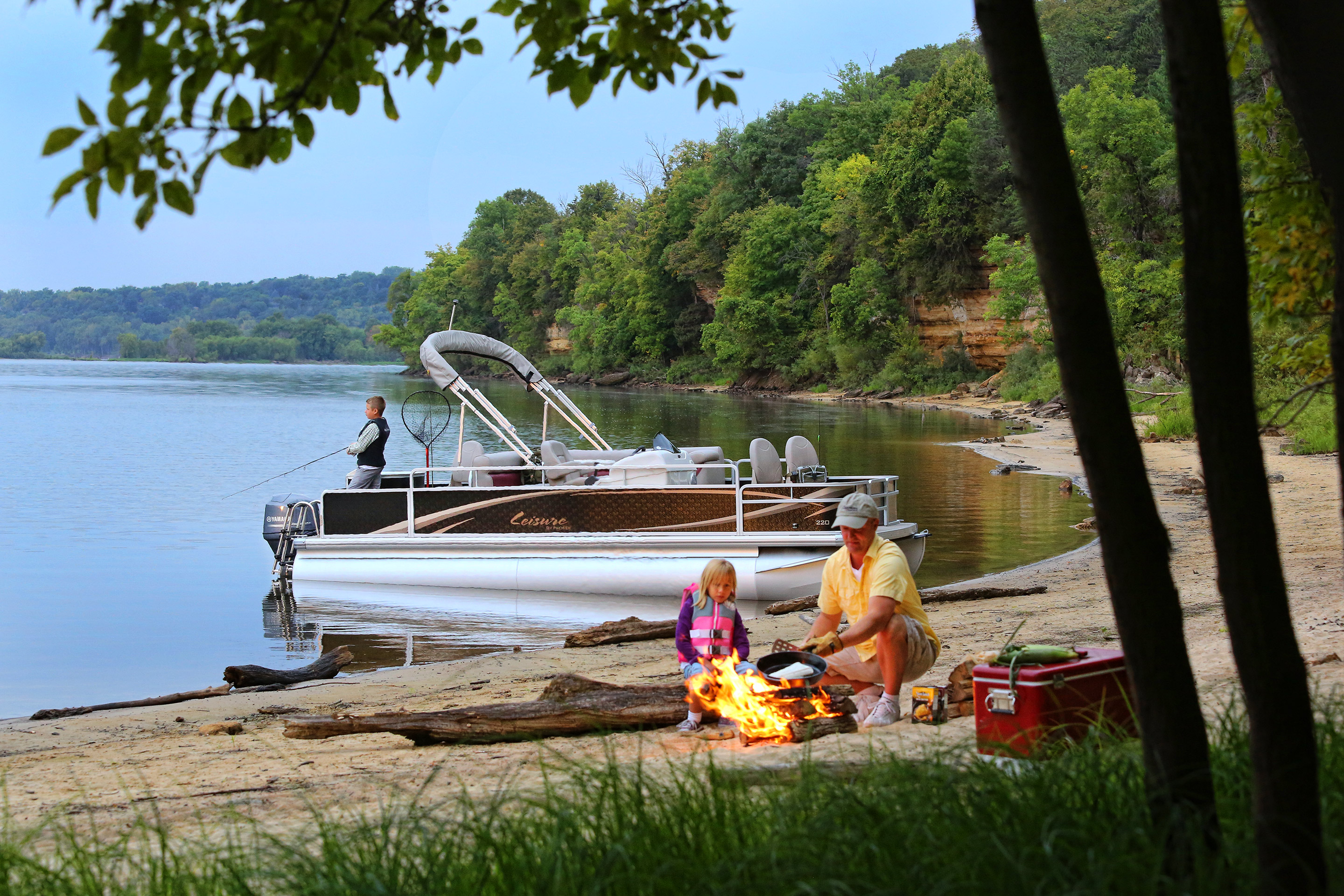 Premier Pontoons, Leisure 220NAV, St. Croix River, Stillwater, MInnesota. Father with kids fishing and cooking fish. Coleman cooler, fire, beach, cliff, bluff